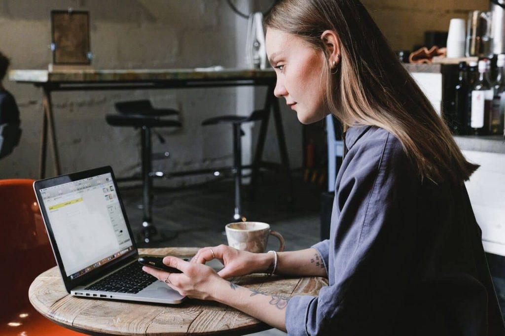 cô gái uống cafe làm việc với laptop